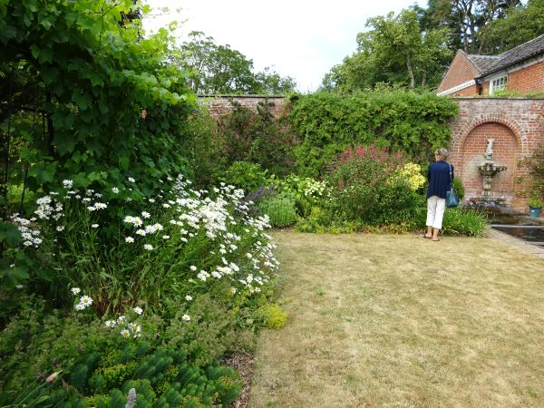 Lawn with flower beds to left and water feature in brick wall and visitor at rear.