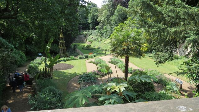 Formal garden with paths surrounded by trees.