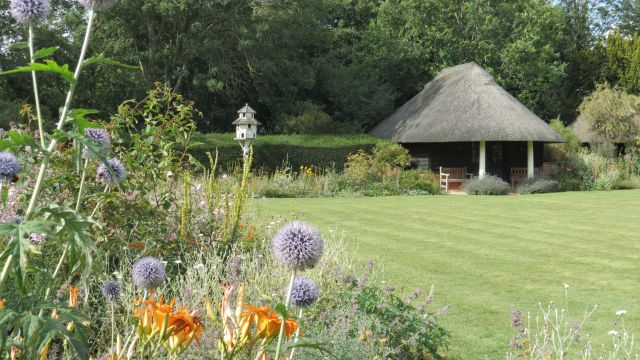 Lawn with flower beds and thatched shelter.