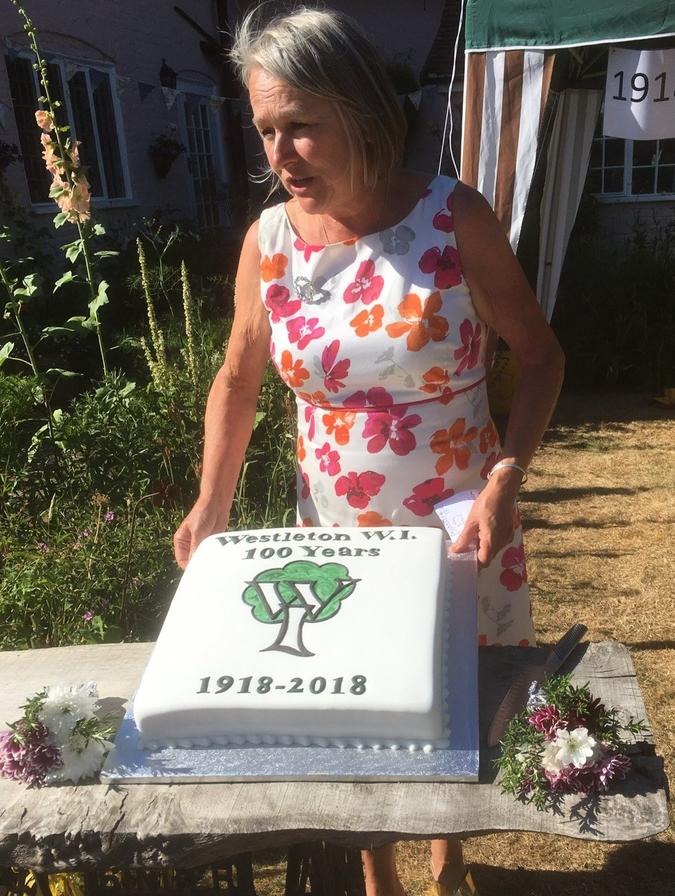 WI Branch President speaking behind centenary cake.