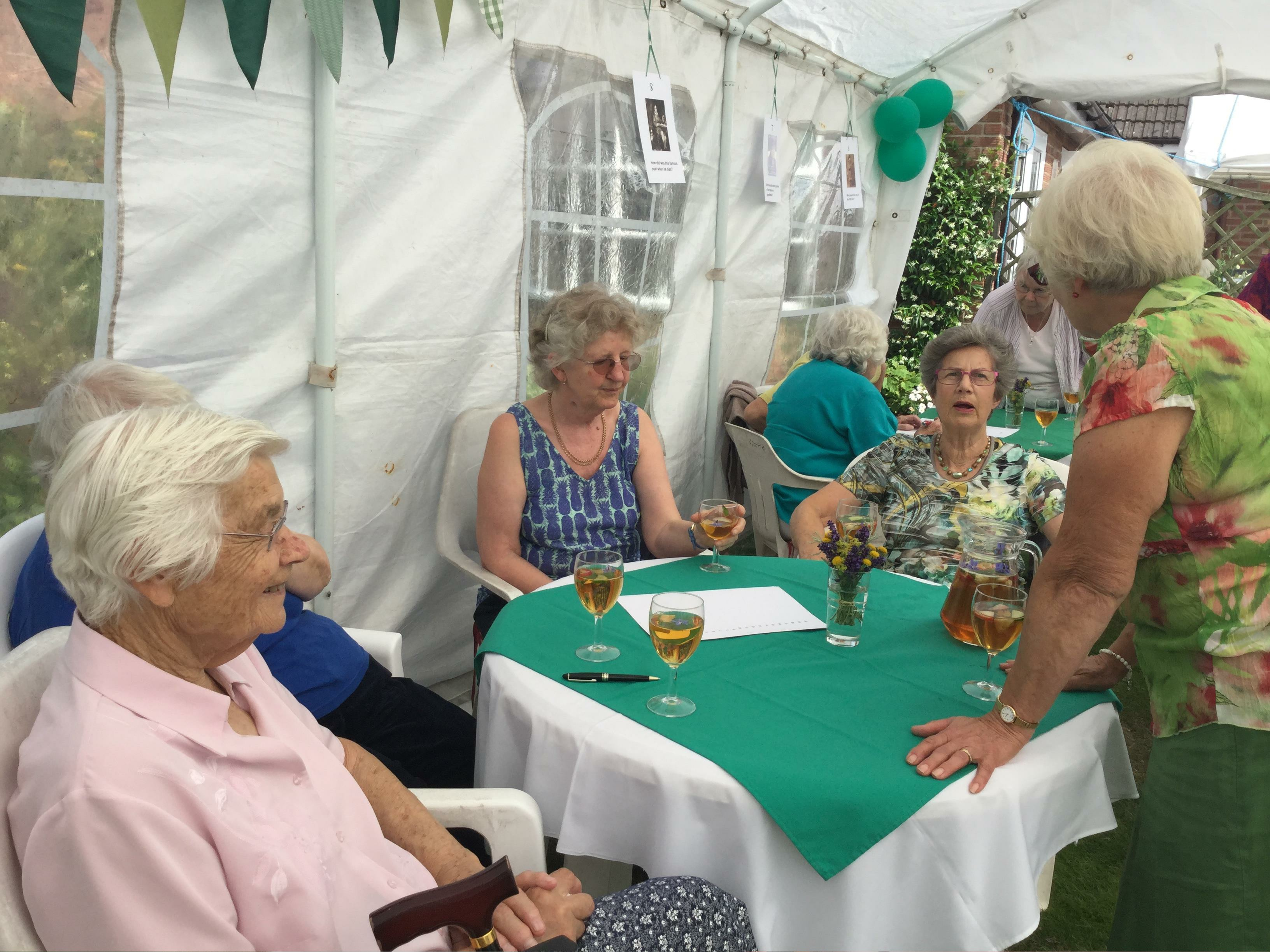 Pimms, Raffle and a Quiz in President Pat Swindell's garden. Members round a table.
