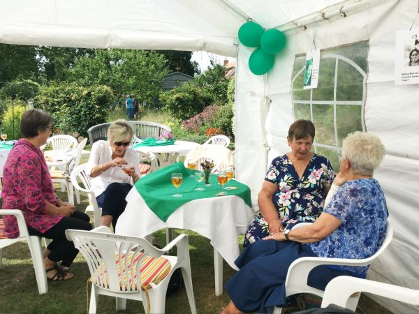 Pimms, Raffle and a Quiz in President Pat Swindell's garden. More members at table with view of garden behind.