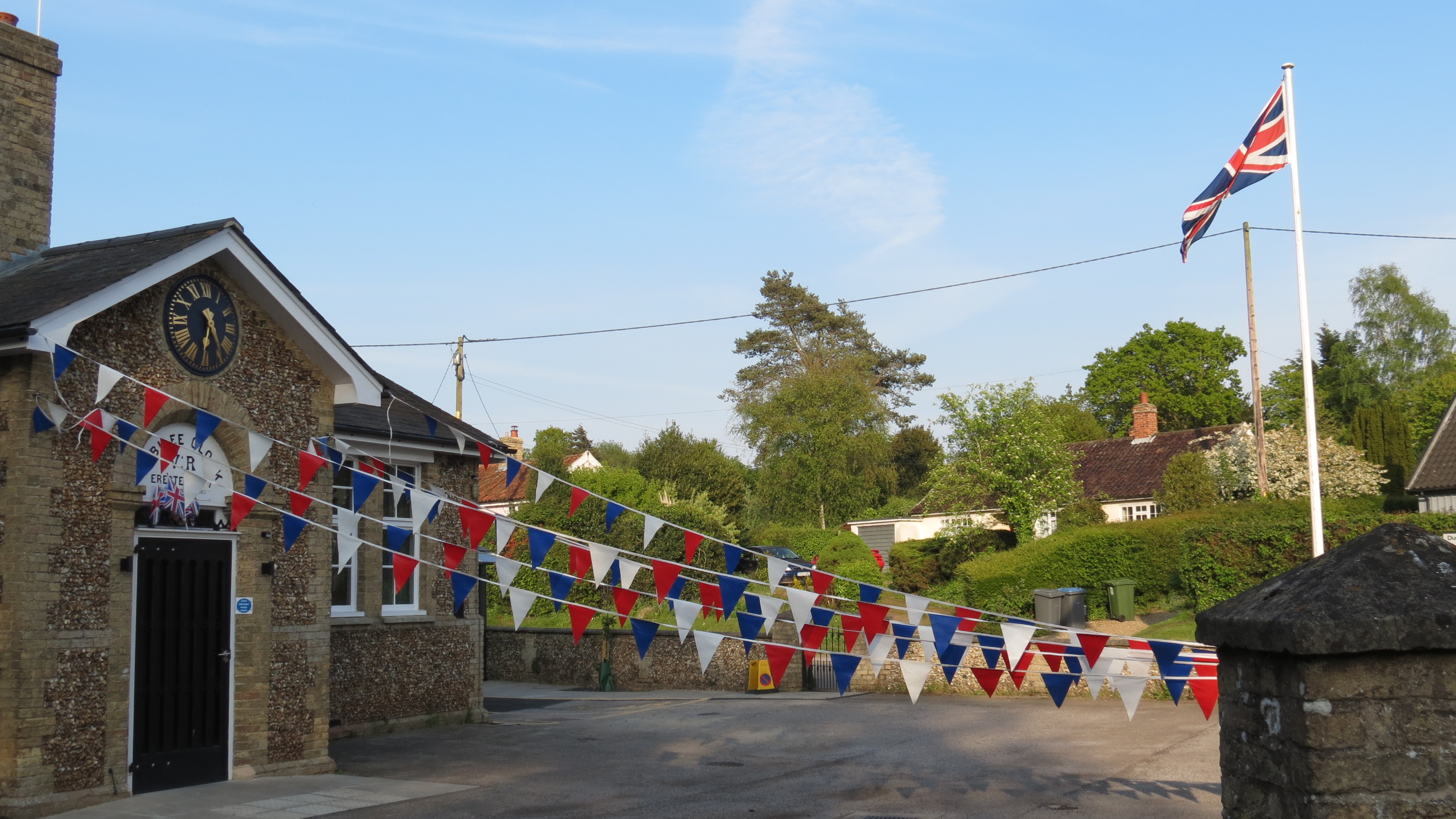 Westleton Village Hall from Darsham Road showing red, white and blue bunting and the flag pole with Union Flag flying.